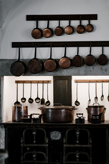 A rack mounted on a kitchen wall to organize pots and pans